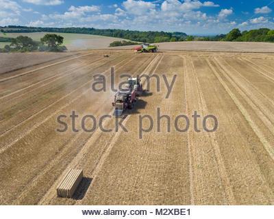 Luftbild des Tractor Pulling Ballenpresse die Strohballen in geernteten Weizen Feld - Stockfoto
