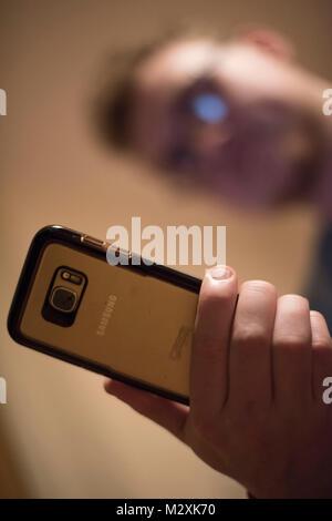 CARDIFF, GROSSBRITANNIEN. Februar 2018. Junger Mann, der ein Telefon benutzt. Die sich ständig weiterentwickelnde - Stockfoto