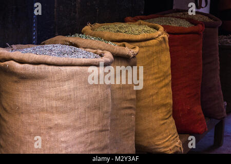 Zeile der hessischen Säcke von Kräutern und Gewürzen für den Verkauf in den Märkten Souks von Marrakesch, Marokko. - Stockfoto
