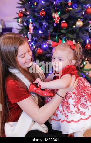 12-jährige Mädchen ihrer 13 Monate alten Cousine, die durch ihre leuchtend roten Schuh ist fasziniert Holding - Stockfoto