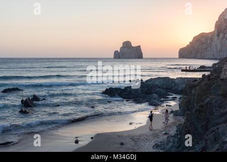 Zwei womans zu Fuß auf den Strand von masua an sunstet mit auf dem Hintergrund der berühmten Felsen namens Pan di - Stockfoto