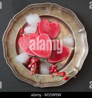 Hausgemachtes Eis in Form der Herzen. Rote Johannisbeere Limonade garniert Minze und Eis auf Metall und schwarzem - Stockfoto