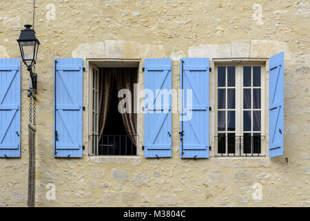 In der Nähe von Windows mit blauen Fensterläden aus Holz auf einem Gebäude in Montreal-du-Gers (Montreal du Gers), - Stockfoto