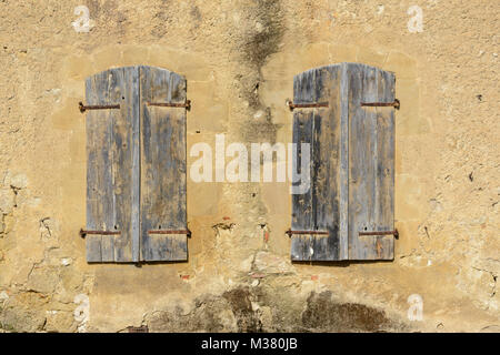 Zwei Fenster mit Fensterläden aus Holz auf einem Gebäude in Barran, Gers (Gascogne), Occitanie (Midi-Pyrénées), - Stockfoto
