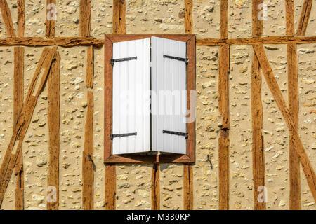 Fenster mit weißen Fensterläden aus Holz auf einem Fachwerkhaus in Barran, Gers (Gascogne), Occitanie (Midi-Pyrénées), - Stockfoto