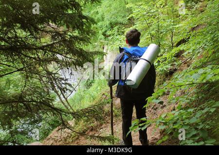 Reisender Mann mit Rucksack ruht auf Flusslandschaft. Lifestyle Reisen glücklich Emotionen Erfolg Konzept Sommerferien - Stockfoto