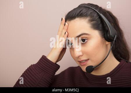 Nahaufnahme Porträt eines verzweifelten jungen Frau hören zu einem Kopfhörer mit Mikrofon während der Arbeit als - Stockfoto