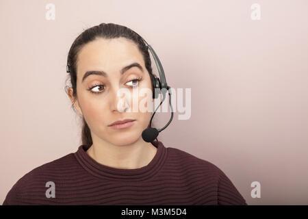 Skeptisch Help Desk oder Call Center Betreiber um ein Gespräch auf der Seite mit hochgezogenen Augenbrauen und eine - Stockfoto