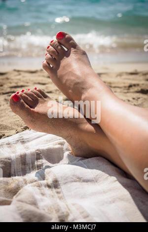 Gallipoli (Italien), August 2017. Sandigen Füßen von einem Mädchen, das Entspannen am Strand. Hochformat. - Stockfoto