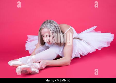 Hübsche Blondine Ballerina sitzend und Stretching auf rosa Hintergrund. - Stockfoto
