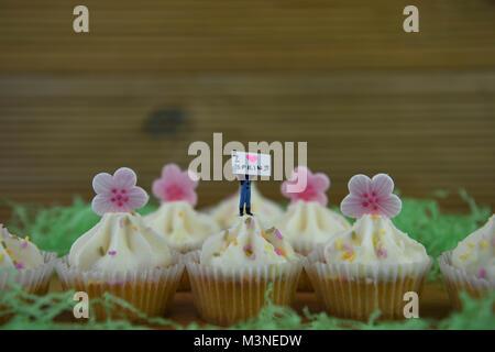Frühling essen leckere Cupcakes mit Miniatur person Figürchen auf Top mit Zeichen für Hallo Frühling und iced Blumen - Stockfoto