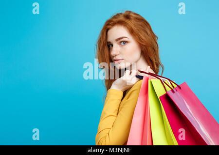 Shopping Konzept - Nahaufnahme Portrait Junge schöne attraktive Haar Mädchen an der Kamera schaut. Blau Pastell - Stockfoto