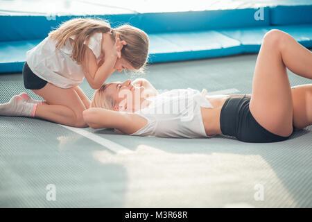 Mutter und kleinen Mädchen spielen am Spielplatz und liegen auf einem Trampolin - Stockfoto