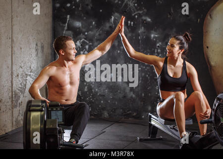 Der Mann und die Frau eine hohe - fünf während der Übungen mit Rudergerät - Stockfoto
