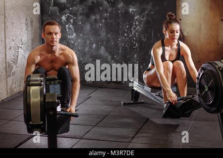 Paar Übungen mit Rudergerät - Stockfoto