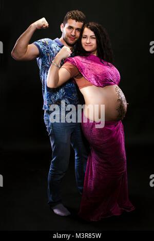 Ehepaar warten auf ein Kind, ein Sport Menschen und schwangere Frau sind Aprilscherze auf schwarzem Hintergrund - Stockfoto