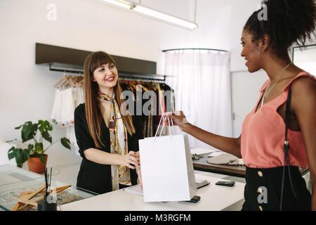Kunden shopping Designer Verschleiß an eine Modeboutique. Unternehmerin Übergabe Warenkorb zu den Kunden. - Stockfoto