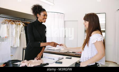 Kunden shopping Designer Verschleiß an eine Modeboutique. Kunden die Zahlung mit einer Kreditkarte. - Stockfoto