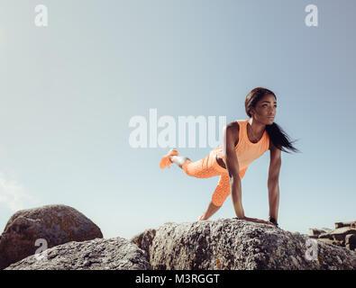 Schwarzes Weibchen zu tun Stretching Übungen auf den Felsen am Strand an einem Sommermorgen. Passende Frau ihr Bein - Stockfoto