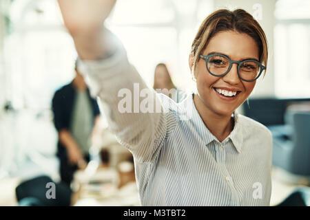 Lächelnden jungen Geschäftsfrau hohe Fiving, während in einem Büro mit Kollegen im Hintergrund arbeiten - Stockfoto