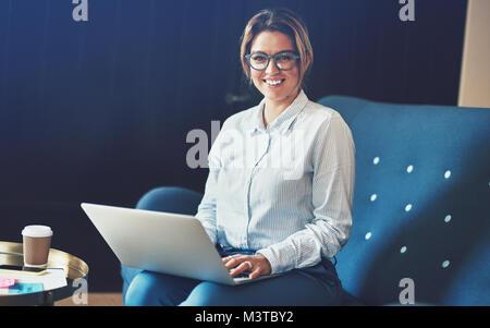 Junge weibliche Unternehmer selbstbewusst lächelnd, während er auf dem Sofa, die von zu Hause aus arbeiten mit einem - Stockfoto