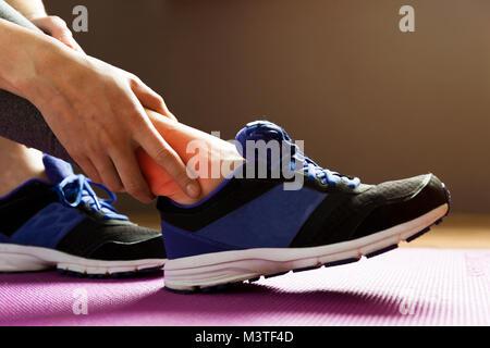 Junge Frau mit einer Knöchelverletzung beim Trainieren. Sport Übung Verletzungen Konzept. - Stockfoto
