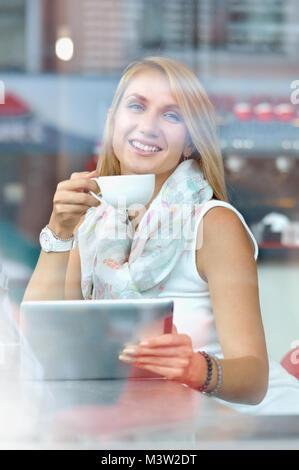 Yyoung Geschäftsfrau auf Touch Pad Bildschirm schaut beim Stehen in der modernen Cafe. Charmante intelligente Frau - Stockfoto