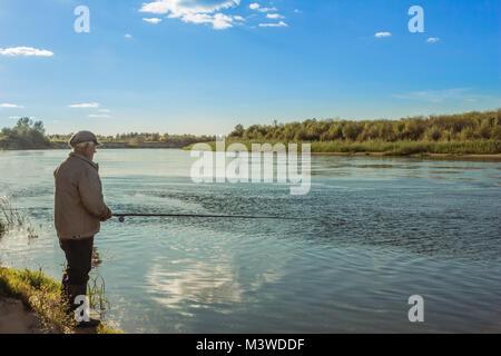 Ein älterer Mann auf eine Angeltour steht am Ufer des Flusses am Abend - Stockfoto