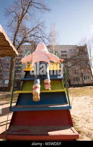 Das Kind krabbelt die Treppen hinauf zum Hügel der Kinder auf dem Spielplatz im Hof - Stockfoto