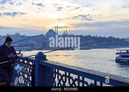 Im Galata Brücke in Istanbul - Januar, 8 2018: Leute angeln auf der Galata-brücke mit Süleymaniye-moschee Hintergrund - Stockfoto