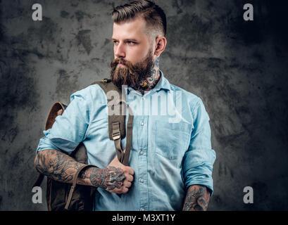 Ein Mann mit Tattoos auf seine Arme und Hals mit Rucksack auf seinem Bac - Stockfoto