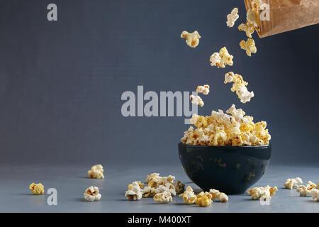 Popcorn fliegen in die Schüssel aus braunem Papier Paket über grauen Hintergrund. Platz für Ihren Text - Stockfoto