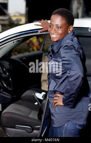 Junge Mechanikerin stand neben dieser Wagen ist glücklich, die aufschlüsselung zu vereinbaren. - Stockfoto