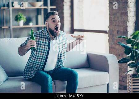 Omg! Ziel! Crazy lustig Fröhlich aufgeregt erstaunt staunen Kerl in kariertem Hemd und Jeans bekleidet, er ist essen - Stockfoto