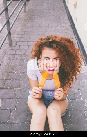 Rothaarige junge Frau essen Eis im Sommer Stockfoto