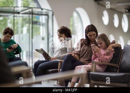 Frauen in einem überfüllten Krankenhaus Wartezimmer warten - Stockfoto