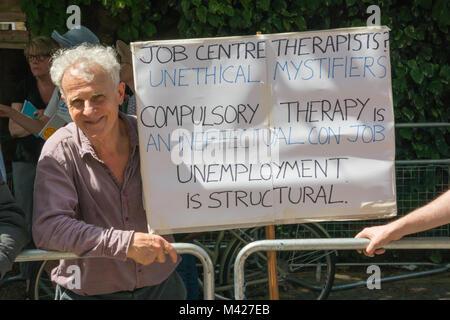 """Psychische Gesundheit Widerstand Netzwerk Demonstrant hält ein Plakat """"Job Center Therapeuten? Unethische Mystifiers. - Stockfoto"""