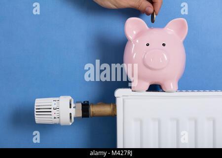 Nahaufnahme der Person Mann einfügen Münze in Piggy Bank gehalten am Kühler - Stockfoto
