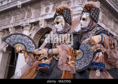 Zwei Frauen in traditionellen Kostümen und Masken, dekoriert mit Fans, vor den Arkaden am Markusplatz stehen während - Stockfoto