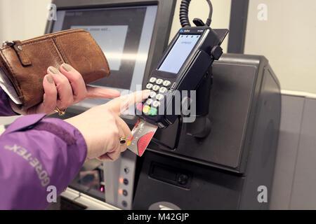 Eine weibliche Shopper mit einem Chip-und-PIN-Kartenlesegerät Maschine für die Waren per Kreditkarte zu bezahlen. - Stockfoto