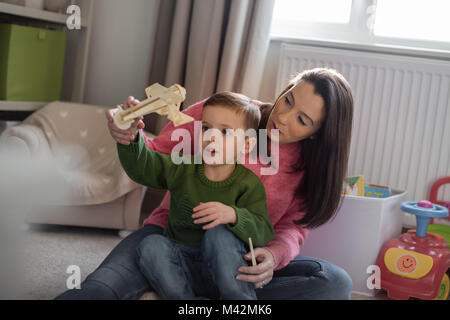 Mutter und Sohn spielen mit Spielzeug Flugmodell - Stockfoto