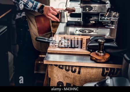 Ein Mann Vorbereitung Cappuccino in einer Kaffeemaschine. - Stockfoto