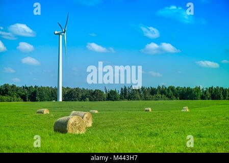 Szene Sommer wind turbine in der Mitte der Wiese voller Strohballen, neben Wald, während der schönen Sonnenuntergang - Stockfoto