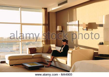 Geschäftsfrau mit Laptop in der Lounge des Hotel Schlafzimmer - Stockfoto