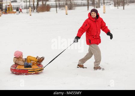 Bild von Vater und Tochter auf Schläuche im Winter Nachmittag im Park - Stockfoto
