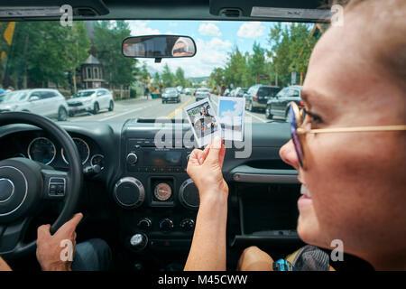 In der Nähe der jungen Frau auf Straße Reise Holding instant Foto, Breckenridge, Colorado, USA - Stockfoto