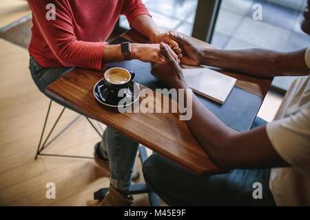 Der Mann und die Frau sitzt an einem Tisch, Hände halten mit einer Tasse Kaffee auf dem Tisch. Zugeschnittenes Bild des Menschen halten sich an den Händen einer Frau sitzt an einem Co