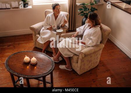 Zwei Frauen reden während des Wartens auf Spa. Weibliche Freunde im Bademantel saß auf Stuhl in Kräutertee und Chatten. - Stockfoto
