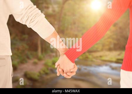 Zusammengesetztes Bild des Paares Händchenhalten Rückansicht - Stockfoto