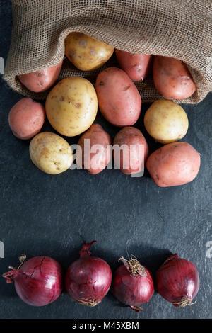 Rot und Gold Kartoffeln im hessischen Sack mit roten Zwiebeln auf schiefer Tischplatte mit Kopie Raum - vertikale - Stockfoto
